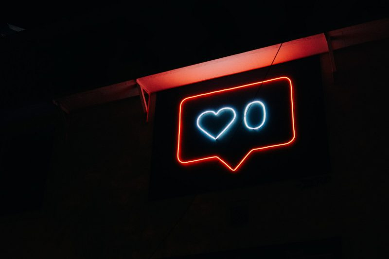 Neon sign with heart and number zero in chat bubble by Prateek Katyal