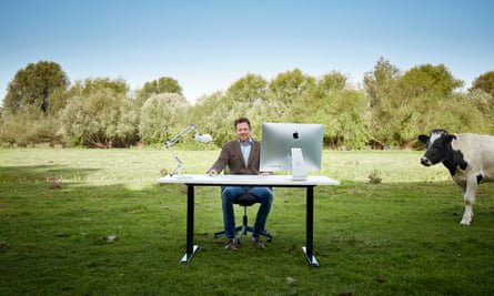 Man in field sitting at desk and computer