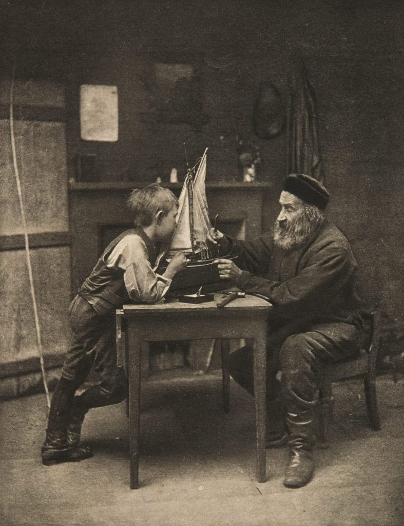 Vintage photograph of an old man building a model ship with a young boy